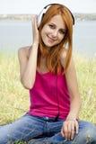 Redhead girl with headphone Stock Photography
