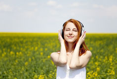 Redhead girl with headphone at field. Royalty Free Stock Images