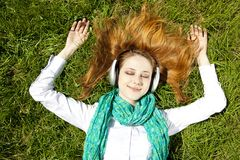 Redhead girl with headphone lies in the park Stock Image