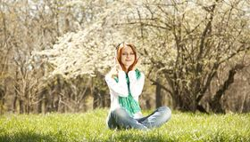 Redhead girl with headphone in the park Royalty Free Stock Photos