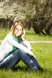 Redhead girl with headphone in the park Royalty Free Stock Photo