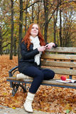Redhead girl with headphones listen music on player in city park, fall season Stock Photography