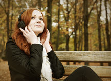 Redhead girl with headphones listen music on player in city park, fall season Royalty Free Stock Images