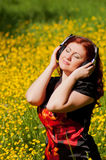Redhead girl with headphones listening to music Royalty Free Stock Photos