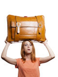 Redhead girl with heavy old suitcase. Royalty Free Stock Images