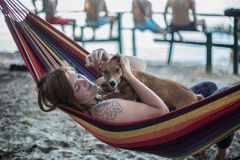 Redhead girl and her dog lying on a lounge at the beach in summer Royalty Free Stock Photography