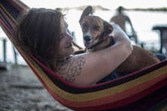 Redhead girl and her dog lying on a lounge at the beach in summer Stock Images