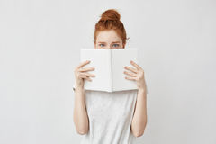 Redhead girl hiding face behind notebook looking at camera frightenedly. Stock Photo