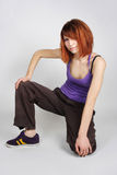Redhead girl in hip-hop clothes sitting Stock Image