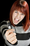 Redhead girl holding a flash drive at camera. Beautiful redhead girl holding an usb memory stick or flash drive at the camera with an angry expression. Studio royalty free stock photo