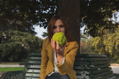 Redhead girl holding a fruit in her hand Royalty Free Stock Images