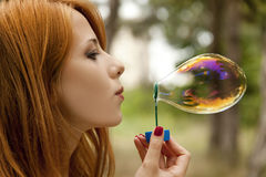 Redhead girl inflate soap bubble Stock Photography