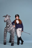 Redhead girl jockey dreams of horses. Redhead girl with freckles in riding clothes and helmet on a light background with a bouncy horse, the jockey concept Stock Photo