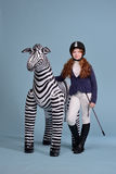 Redhead girl jockey dreams of horses. Redhead girl with freckles in riding clothes and helmet on a light background with a bouncy horse, the jockey concept Royalty Free Stock Image