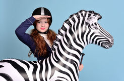 Redhead girl jockey dreams of horses. Redhead girl with freckles in riding clothes and helmet on a light background with a bouncy horse, the jockey concept Stock Photography