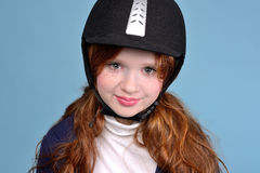 Redhead girl jockey. Modest red-haired girl with freckles in a jockey helmet, jockey concept Royalty Free Stock Images