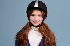 Redhead girl jockey. Smiling red-haired girl with freckles in a jockey helmet, jockey concept Stock Images