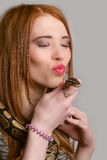 Redhead girl kisses a snake. Girl holds in the hands of a python and kisses him Royalty Free Stock Photography