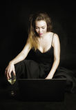 Redhead girl with laptop and glass of wine stock photo