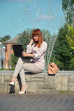 Redhead girl with laptop sitting on the fountain. Young red-haired girl in a white suit, sitting with a laptop on the background of the fountain Stock Images