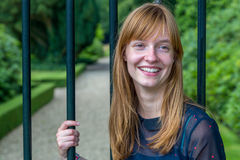 Redhead girl laughing holding metal bars of entry gate Stock Images