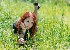 Redhead girl lay on grass. Stock Photo