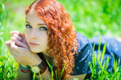 Redhead girl lay on grass. Stock Photography
