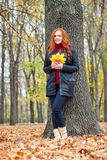 Redhead girl with leaf in city park, fall season Royalty Free Stock Photography