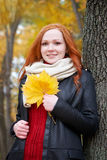 Redhead girl with leaf in city park, fall season Stock Image