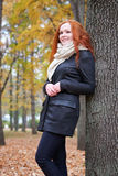 Redhead girl with leaf in city park, fall season Royalty Free Stock Images