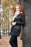Redhead girl with leaf in city park, fall season Stock Images