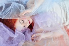 Redhead girl in a light air colored dress lies on the floor, a p Stock Photos