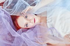 Redhead girl in a light air colored dress lies on the floor, a portrait close-up. Romantic woman with long hair and cloud dress. Girl dreams, bright makeup Stock Image