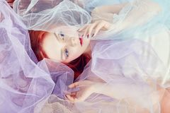 Redhead girl in a light air colored dress lies on the floor, a portrait close-up. Romantic woman with long hair and cloud dress. Girl dreams, bright makeup Royalty Free Stock Photos