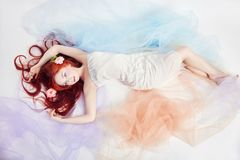 Redhead girl in light airy colored dress lies on the floor white background. Beautiful flowers in girl hair. Romantic woman. With long hair and cloud dress Stock Image