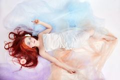 Redhead girl in light airy colored dress lies on the floor white Stock Photo