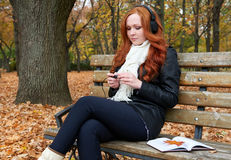 Redhead girl listen music in city park, fall season Stock Images