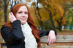 Redhead girl listen music in city park, fall season Royalty Free Stock Image