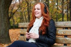Redhead girl listen music in city park, fall season Stock Photography