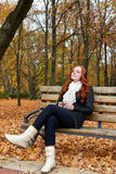 Redhead girl listen music in city park, fall season Royalty Free Stock Images