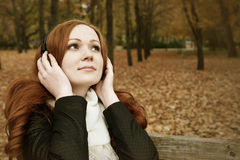 Redhead girl listen music in city park, fall season Royalty Free Stock Photos