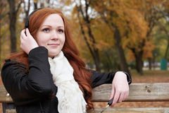 Redhead girl listen music in city park, fall season Stock Photography