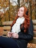 Redhead girl listen music in city park, fall season Stock Photos