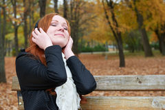 Redhead girl listen music in city park, fall season Stock Images