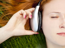 Redhead girl listening music at green grass Stock Image