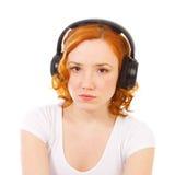 Redhead girl listening music in headphones Royalty Free Stock Photo