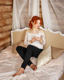 Redhead girl listening to music on headphones Royalty Free Stock Photography