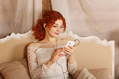 Redhead girl listening to music on headphones Stock Photo