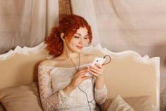 Redhead girl listening to music on headphones Stock Photo