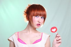 Redhead girl with lollipop heart horizontally Royalty Free Stock Photography